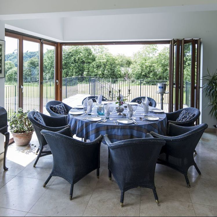 Dining area in open plan living area with bi folding doors to balcony